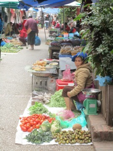 Vendor bundled up to sell her produce.