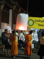 Lighting lanterns to be released in the air for blessings