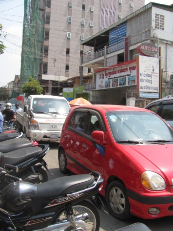 Big cars, motorbikes, and tuk tuks jam Phnom Penh's streets.